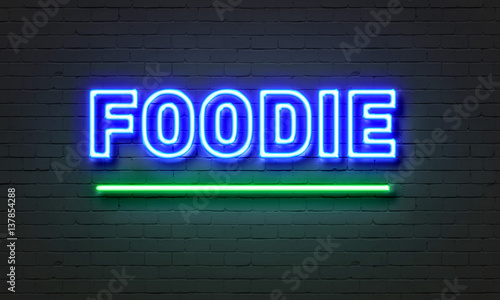 Photo  Foodie neon sign on brick wall background.