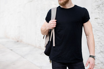 Young muscular bearded man wearing black tshirt and backpack posing outside. Empty white concrete wall on the background. Hotizontal mockup, front view