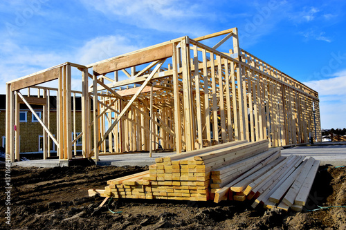 Fotografia, Obraz  Two story wood frame residential building under construction with material in foreground