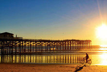 Bicyclist Rides In The Shadows And Orange Colors Of A Stunning San Diego Sunset In California, With Pier In Background.