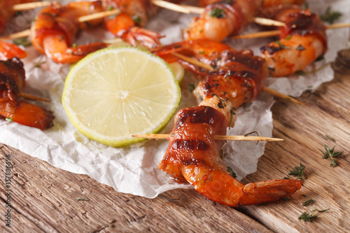 Fotografía  Delicious shrimp wrapped in bacon with spices and lime close up