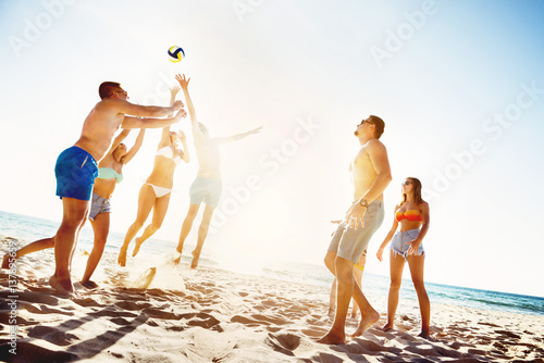 Friends playing beach voleyball sunset time
