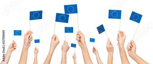 Foto  Hands holding and raising European Union flags