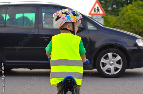 Fotografía  Little boy riding a bike and wearing reflective vest and helmet on the road