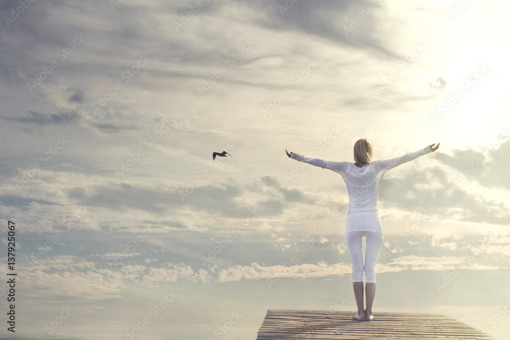 Fototapeta woman with open arms meditating in front of a spectacular sky