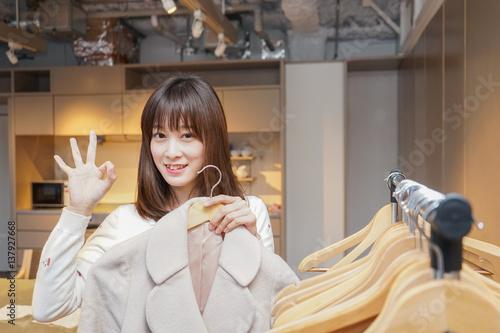 Fotografie, Obraz  Young woman using hanger