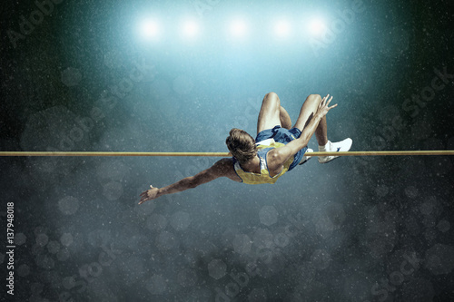 Fotografiet Athlete in action of high jump.
