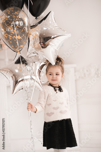 Smiling Baby Girl 5 6 Year Old Holding Silver Star Balloons In White Room Wearing Knitted Sweater With Hearts And Black Dress Birthday Party See More