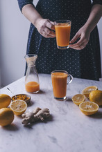 Woman Holding A Glass Of Orange, Lemon And Carrot Juice With Turmeric And Ginger
