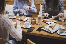Three Unrecognisable Women Having Breakfast At Coffee Shop.