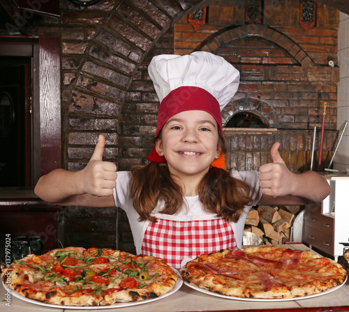 happy little girl cook with pizza and thumbs up in pizzeria