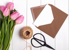 Pink Tulips, Envelope, Scissors And Jute Rope On The White Table