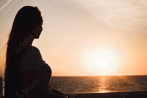 Recess Fitting Zen Beautiful girl looks at the sea a fiery sunset. Silhouette of a girl