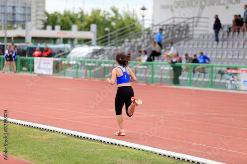 Obraz Dziewczyna biegnie, ściga się po torze na stadionie. - fototapety do salonu