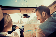 Smiling Man And Woman Using Map On Roadtrip