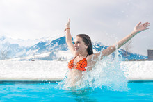 Geothermal Spa. The Girl Enjoys Swimming In Blue Water On The Background Of Snowy Mountains.