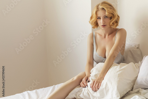 8312f9d96 Beautiful blonde fit woman with make up and curly short hairstyle laying on  bed in underwear