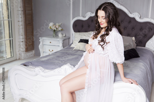 93878f774 Pregnant sexy caucasian white woman with curly hairstyle sitting in luxury  rich interior of her home