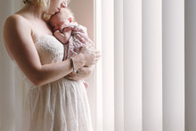 Mother Carrying Daughter While Standing By Window At Home