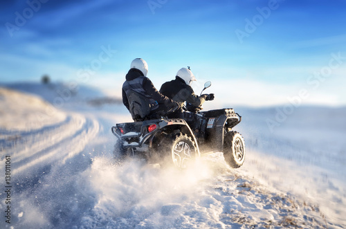 Poster Motorsport Quad bike in motion, ride on top of the mountain on snow. People riding quad bike on mountain at sunset