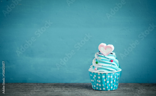 Photo  Cupcake with sweet heart shape of marshmallow against blue background