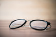 Leinwanddruck Bild - black glasses on wooden table. Close-up a black glasses.
