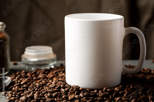 Fotobehang Koffiebonen White coffee mug with coffee beans and glass jar with ground coffee inside
