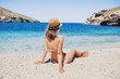 Young woman sitting on the beach and having fun. Vacations lifestyle concept