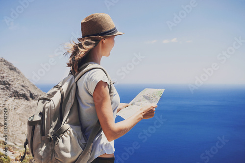 Cuadros en Lienzo Back side of traveler girl standing with map and looking at the sea, travel, hik