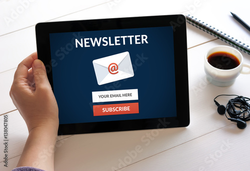 Hand holding digital tablet computer with subscribe newsletter concept on screen. All screen content is designed by me