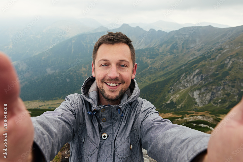 Fototapety, obrazy: Smiling hiker taking a selfie in front of mountain landscape