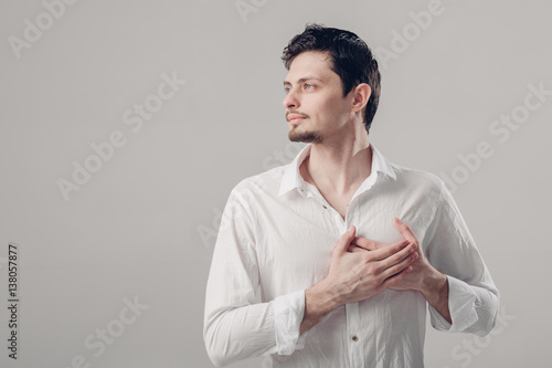 Fotografie, Obraz  handsome young proud man in shirt holding hand on chest on grey