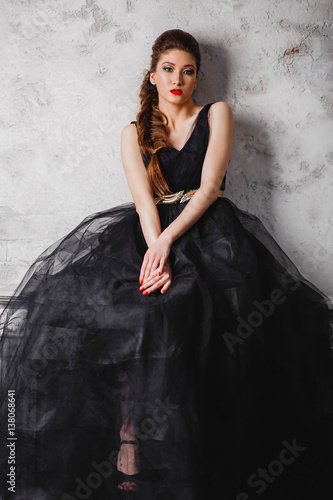Recess Fitting beautiful brunette girl in long black dress makeup red lips and manicure is sitting near the white gray wall looking at the camera