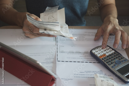 Fotomural man using calculator for  calculate expenses accounts