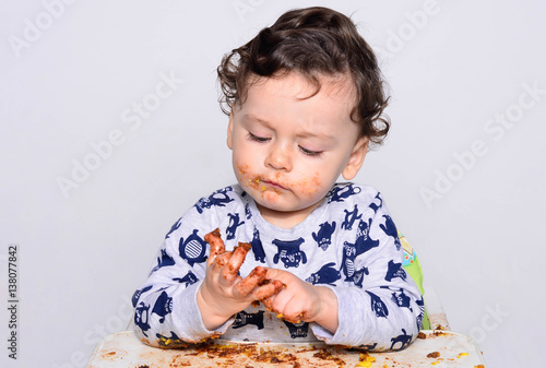 One Year Old Kid Eating A Slice Of Birthday Smash Cake By Himself Getting Dirty