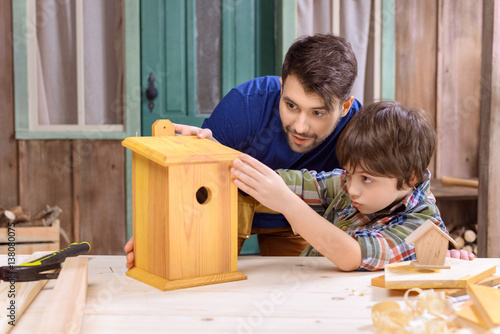 Concentrated father and son making wooden birdhouse together in workshop Poster Mural XXL