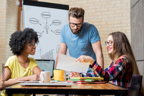 Fotografía  Multi ethnic coworkers dressed casually in colorful clothes working during the m