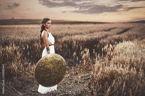 Fotografie, Obraz Brunette wearing in dress like greece style holding shield.