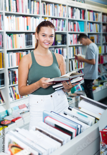 Foto  Teenager girl reading book while choosing new literature