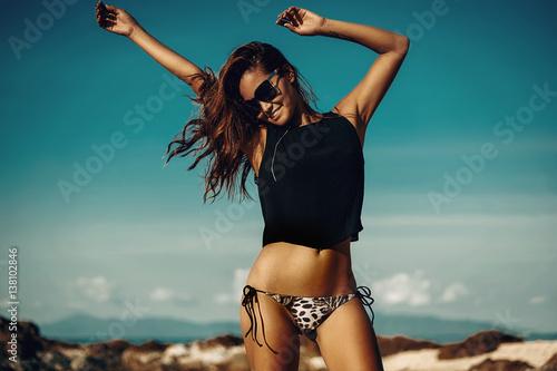 Naklejka premium Piękna partyjna dziewczyna tanczy i macha ręki na plaży nad niebieskim niebem