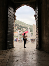 Woman Holding A Pink Umbrella At Dubrovnick Streets In Croatia