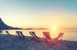Beach loungers on the deserted coast sea at sunrise.