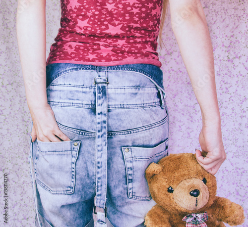 Fotografía de una niña de espaldas a la cámara sujetando un oso de peluche