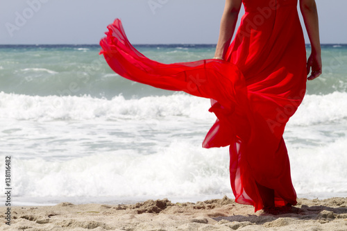 Deurstickers Akt Beautiful red dress flowing in the wind at the beach. Cropped.