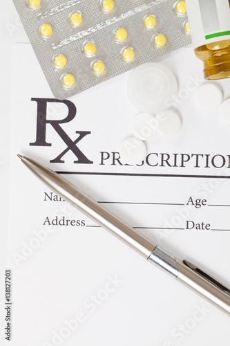 Fotografia  Different pills and silver color pen over medical prescription form