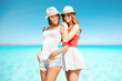 smiling young women in hats on beach