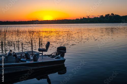 Fotografia, Obraz Fishing boat on tranquil lake at sunset in Minnesota