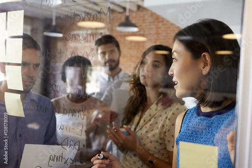 Fotografie, Obraz  Businesswoman Writing Ideas On Glass Screen During Meeting