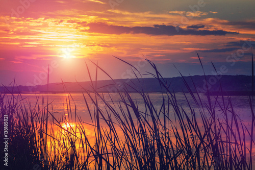 Fototapety, obrazy: majestic sunset over the lake. overcast clouds in the sky ,  grass in sunlight. instagram filter