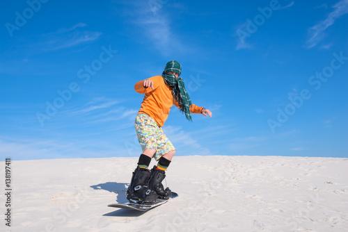 Man snowboarding amongst the sand dunes - unusual use - Buy